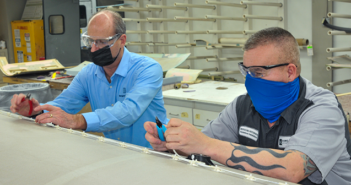 Bongiovi rep Rob Hamelink and Duncan Aviation avionics modifications specialist Ritchie Peterson work on installing transducers for the Bongiovi Aviation audio system